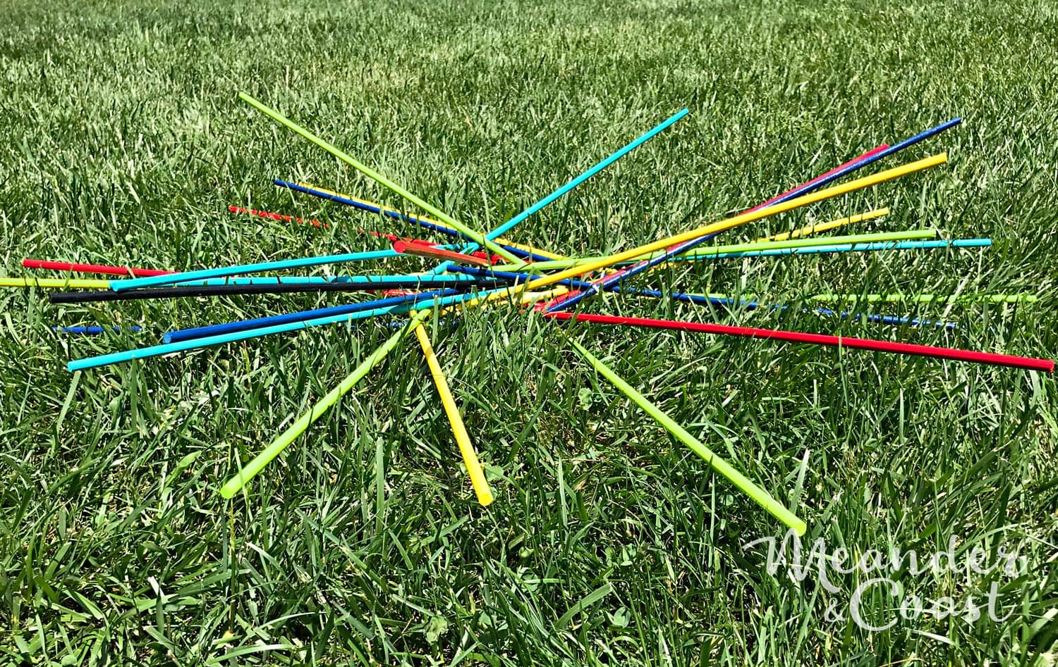 Such a cute game to play outside! Bright colored giant pick up sticks yard game. 15 Minute DIY giant yard game project from Meander & Coast. These would be perfect to take camping this summer! Make a giant outdoor game of pick up sticks. Quick and easy craft. | Meander & Coast #giantgame #pickupsticks #oversizedgame #giantyardgames #bigyardgame #campinggames